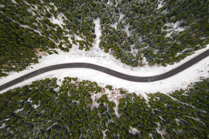 Flight over the winter mountains with road serpentine