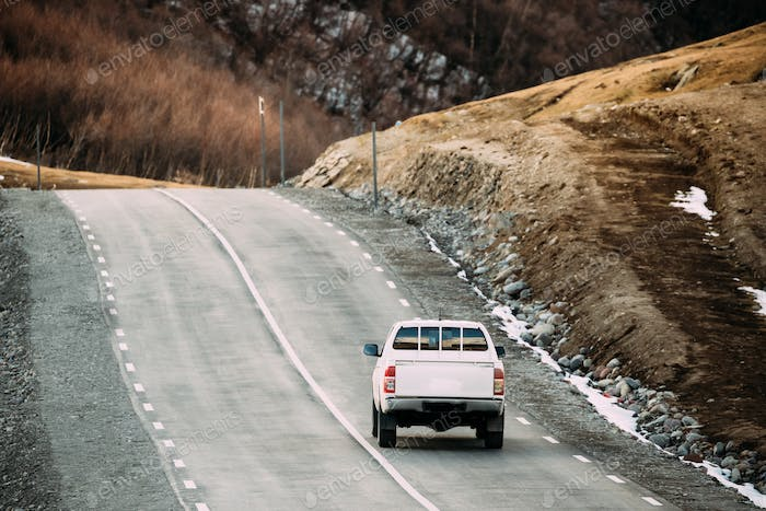 White SUV Car Moving On Mountain Road In Autumn Mountains Landsc