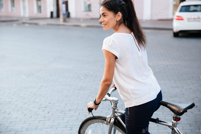 Young brunette woman riding on bicycle in city
