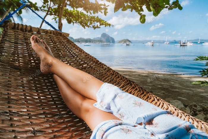 Feet of adult woman relaxing in a hammock on the beach during summer holiday