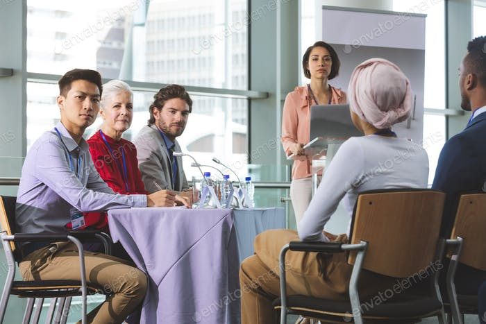 Diverse group of business people looking at camera during a business seminar