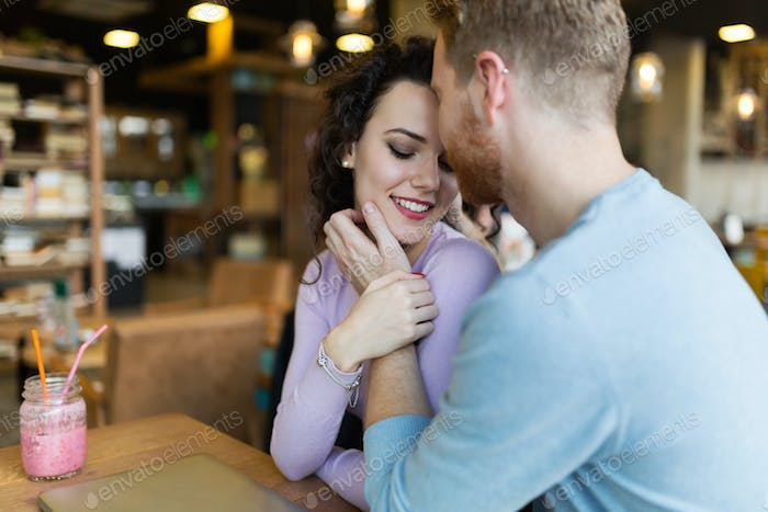 Young happy couple on date in coffee shop