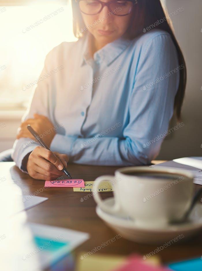 Female entrepreneur writing notes at desk
