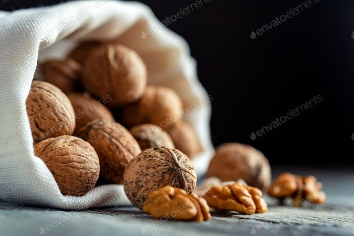 Walnuts in sack on wooden backgound