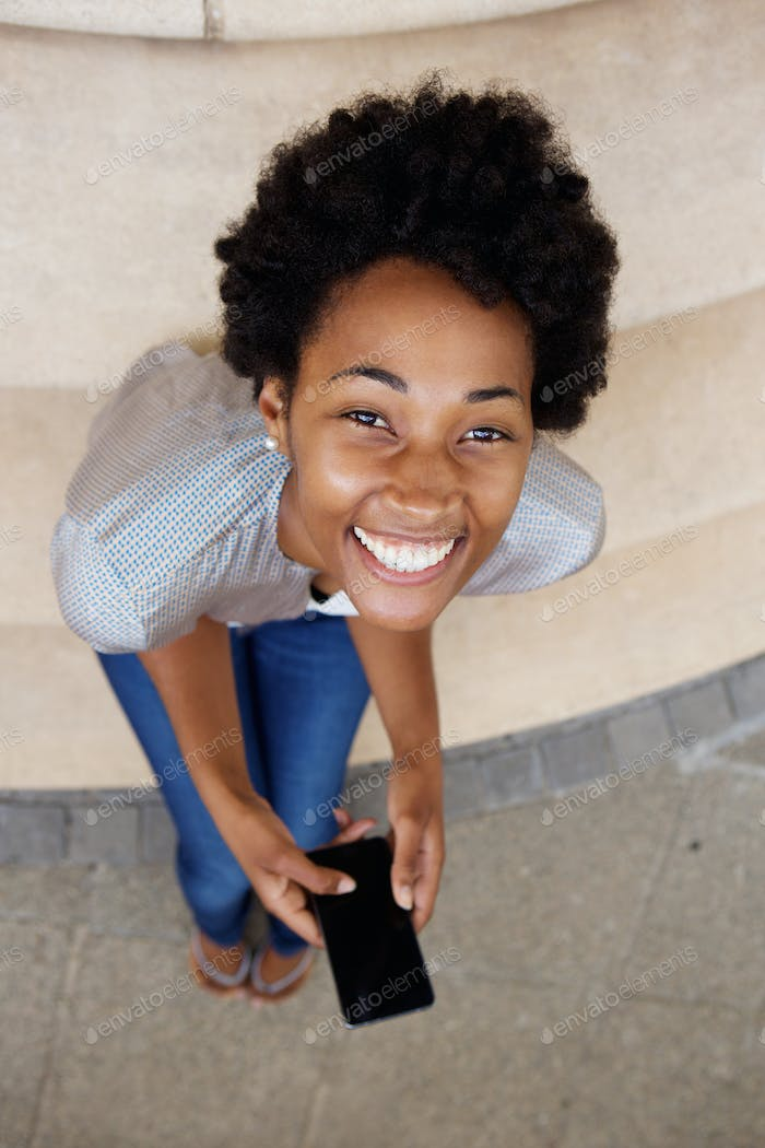 Cheerful young african woman sitting on steps with a mobile phone