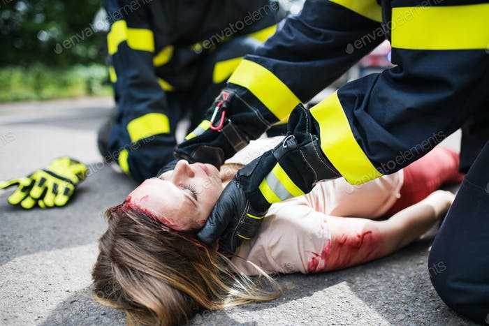 Unrecognizable firefighters helping a young injured woman lying on the road after an accident.