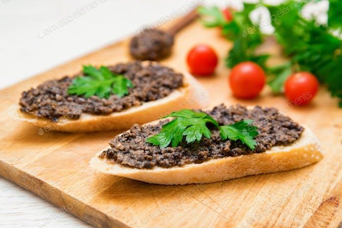 Fresh tasty bruschetta with truffle sauce, parsley and tomates