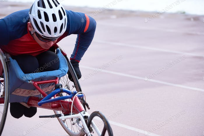 Determined handicapped male athlete in helmet racing in specialized handcycle