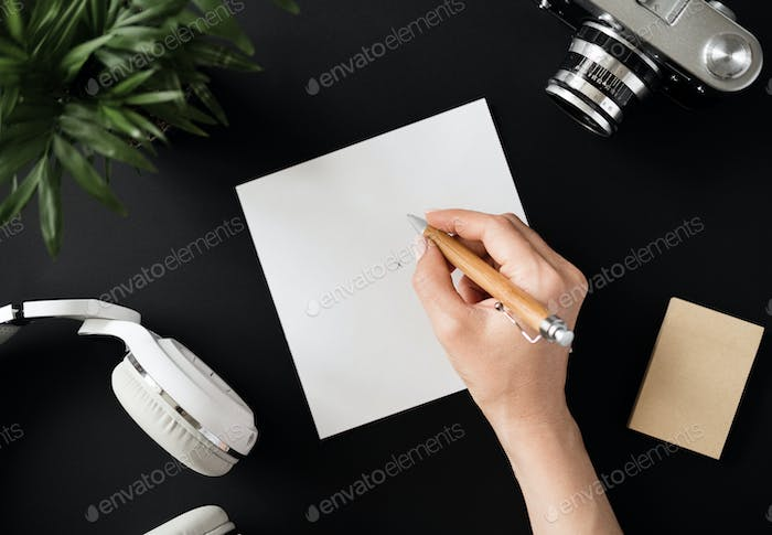 Top view of a flat lay student's hand writes note