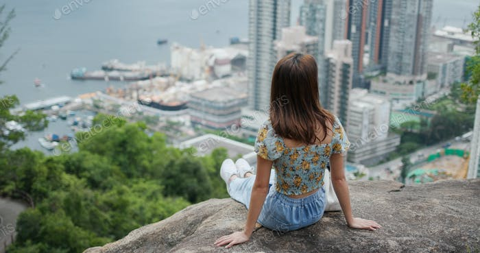 Woman sit at the top of the hill and enjoy the city view