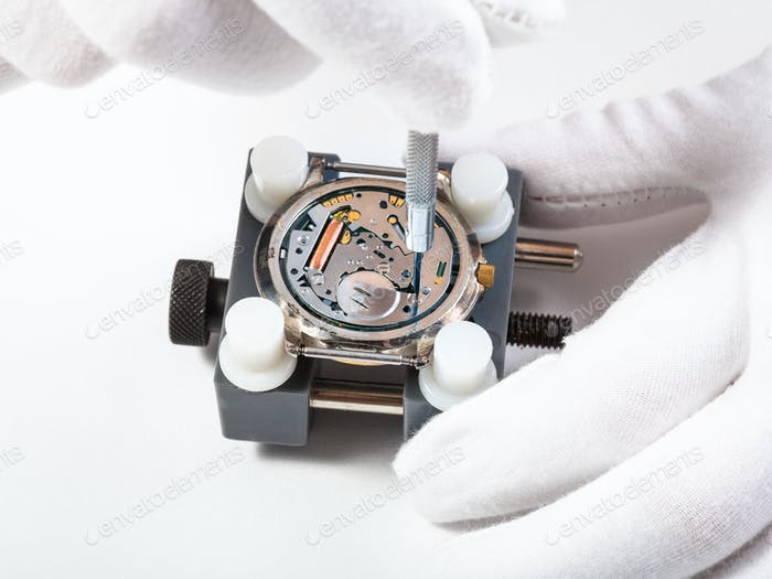 repairing quartz watch close up with screwdriver
