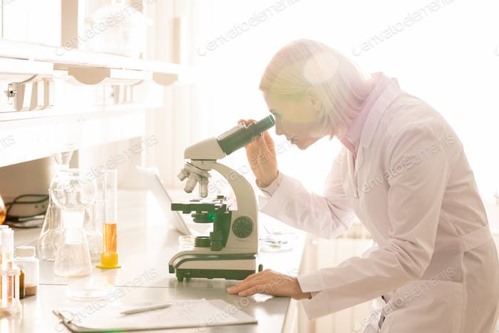 Busy lady studying sample via microscope