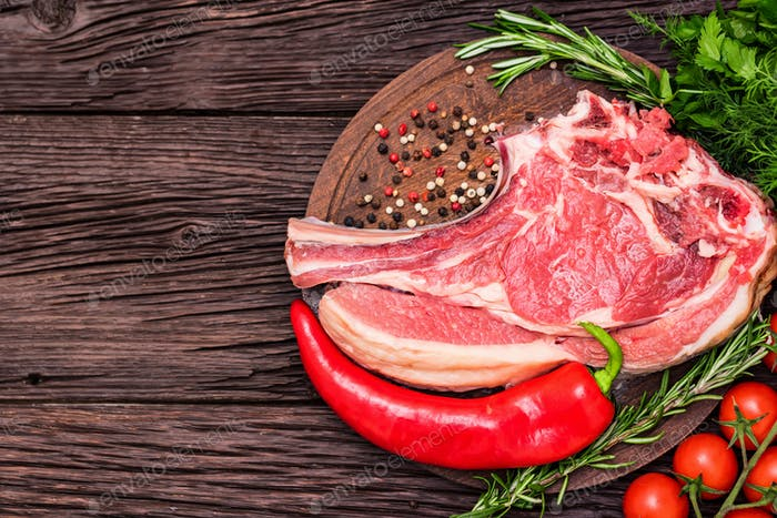 Raw beef steak with pepper, herbs and tomatoes