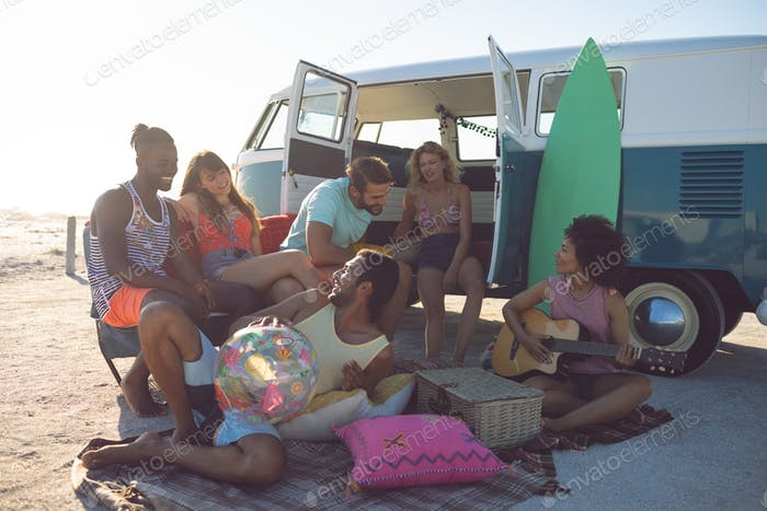 Front view of happy group of diverse friends having fun near camper van at beach