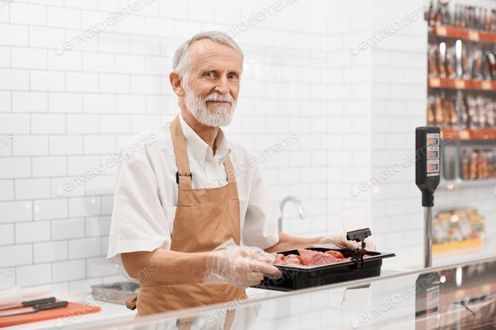 Male butcher demonstrating meat in supermarket