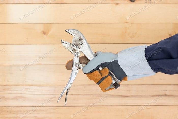 Hand in Handschuh hält verstellbarer Schraubenschlüssel