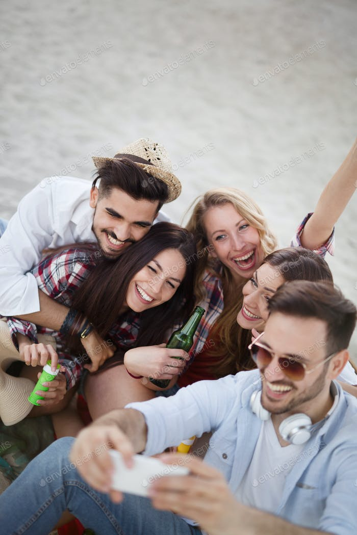 Group of cheerful friends having great time at beach