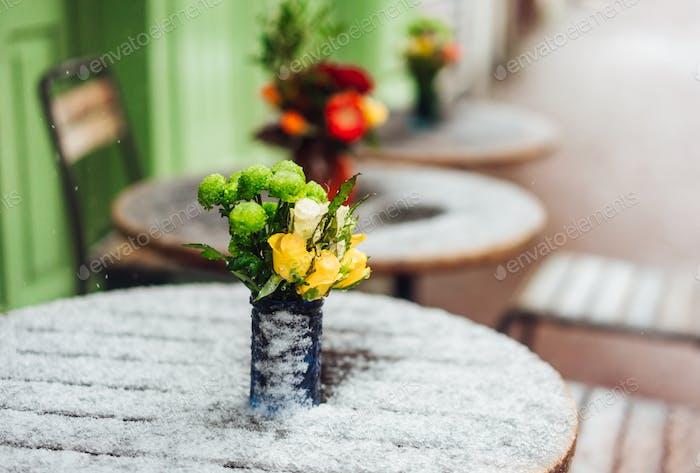 Blumen stehen auf einem verschneiten Tisch