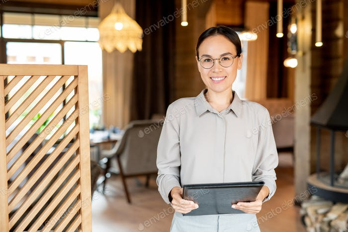 Young smiling businesswoman of Asian ethnicity holding document
