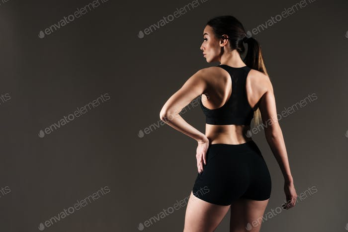 Sportswoman posing over grey background.