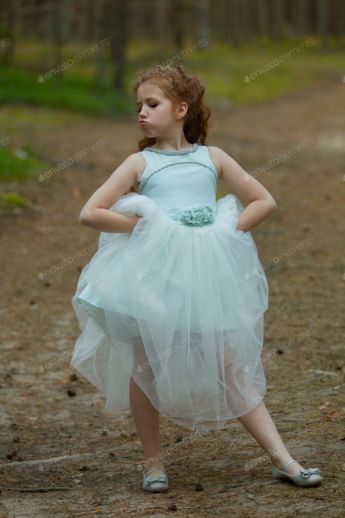Little emotional girl walks in a summer forest in a dress