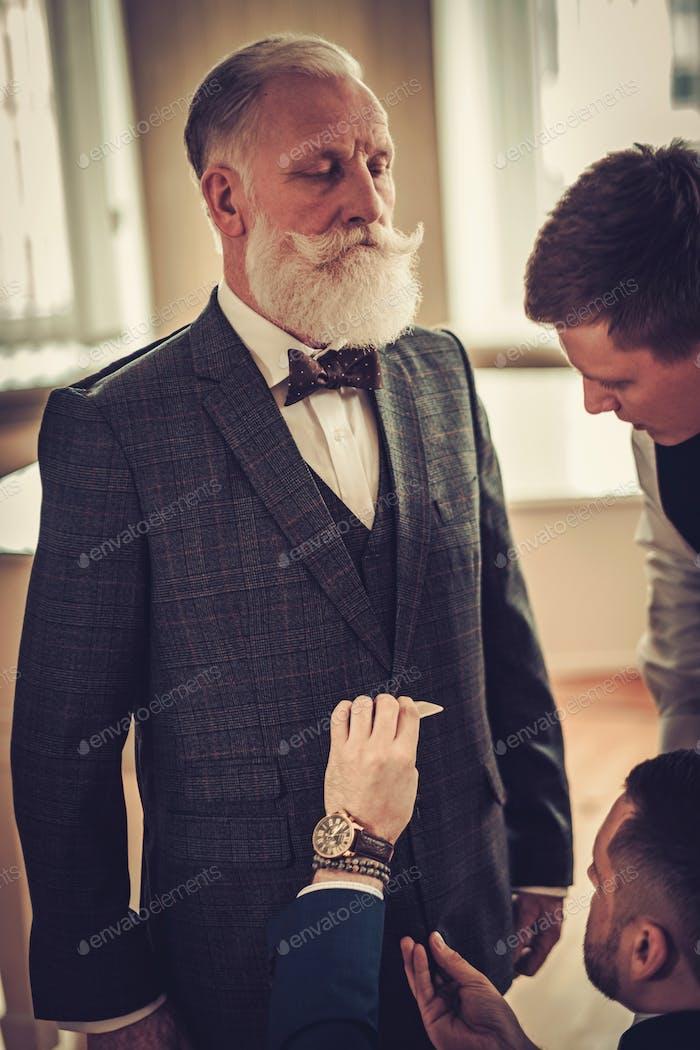 Портной и его ставленник измерения клиента для одежды на заказ