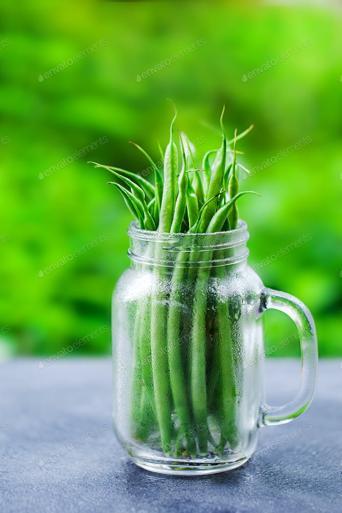 Green Beans in Glass Jar on Grey Table. Summer Outdoor Background.