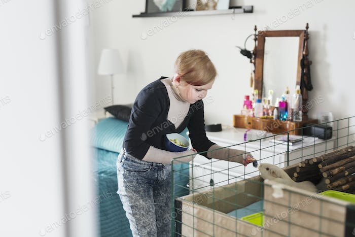 Disabled woman feeding guinea pig
