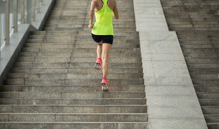 Woman runner running up on stairs of city overpass bridge