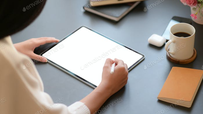 Professional designer is working on tablet to design his future project in comfortable office.