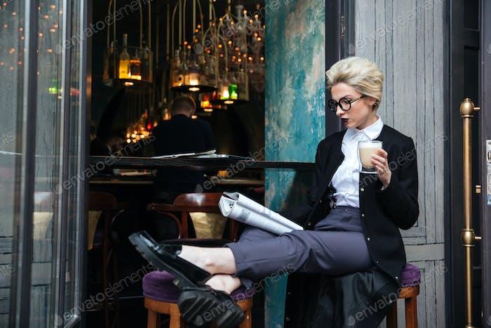 Beautiful stylish girl sitting in cafe and reading magazine