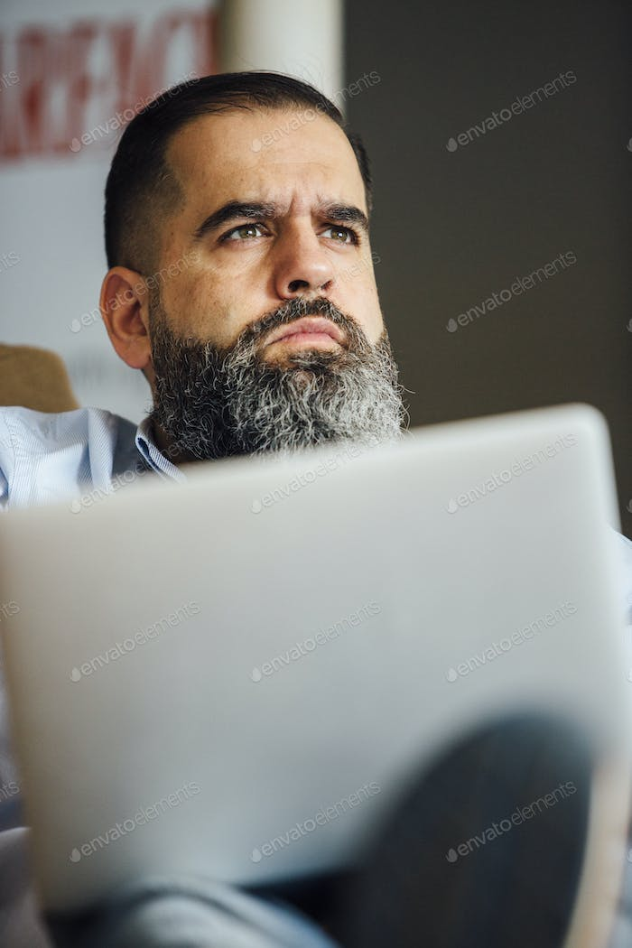 Thoughtful man with laptop