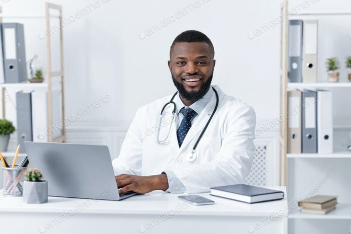 Photo of smiling african american doctor working in clinic