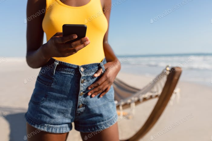 Mid section of African-american woman using mobile phone with her thumbs in belt loops on the beach
