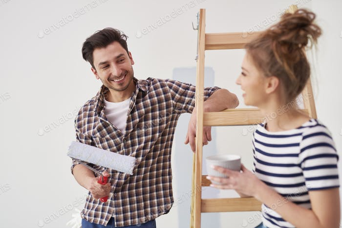 Happy man painting the interior wall in new apartment