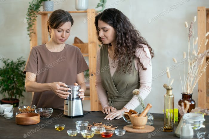 Young woman using electric appliance for grinding ingredients for handmade soap