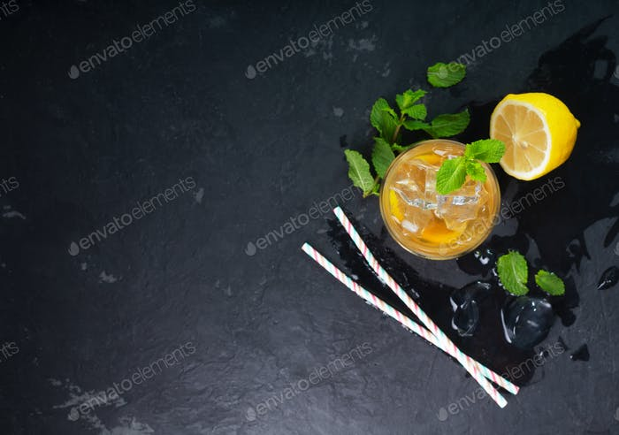 Lemon ice tea on dark background with mint and ice