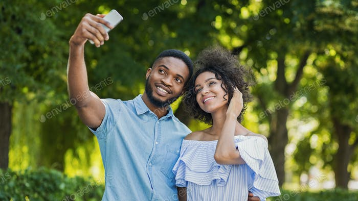Cheerful lovely couple making selfie on smartphone outdoors