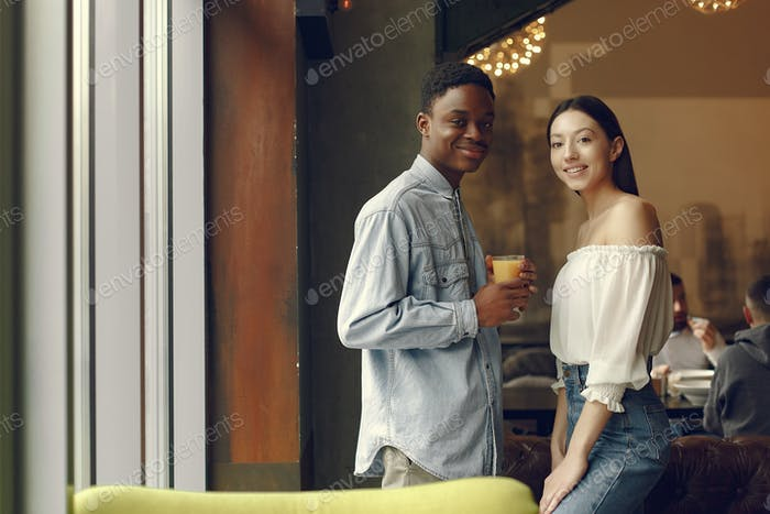 Internationals people standing in a cafe with orange juice