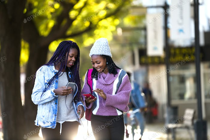 Two beautiful young woman using mobile phone in the street.