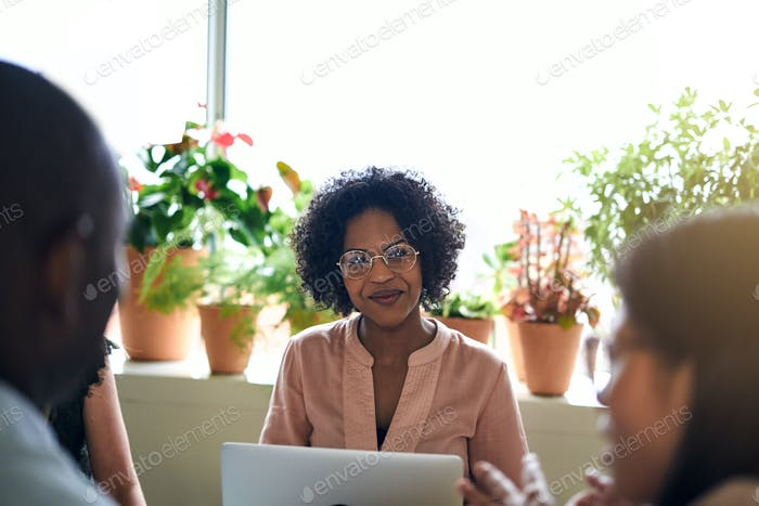 Smiling African businesswoman meeting with colleagues in an office