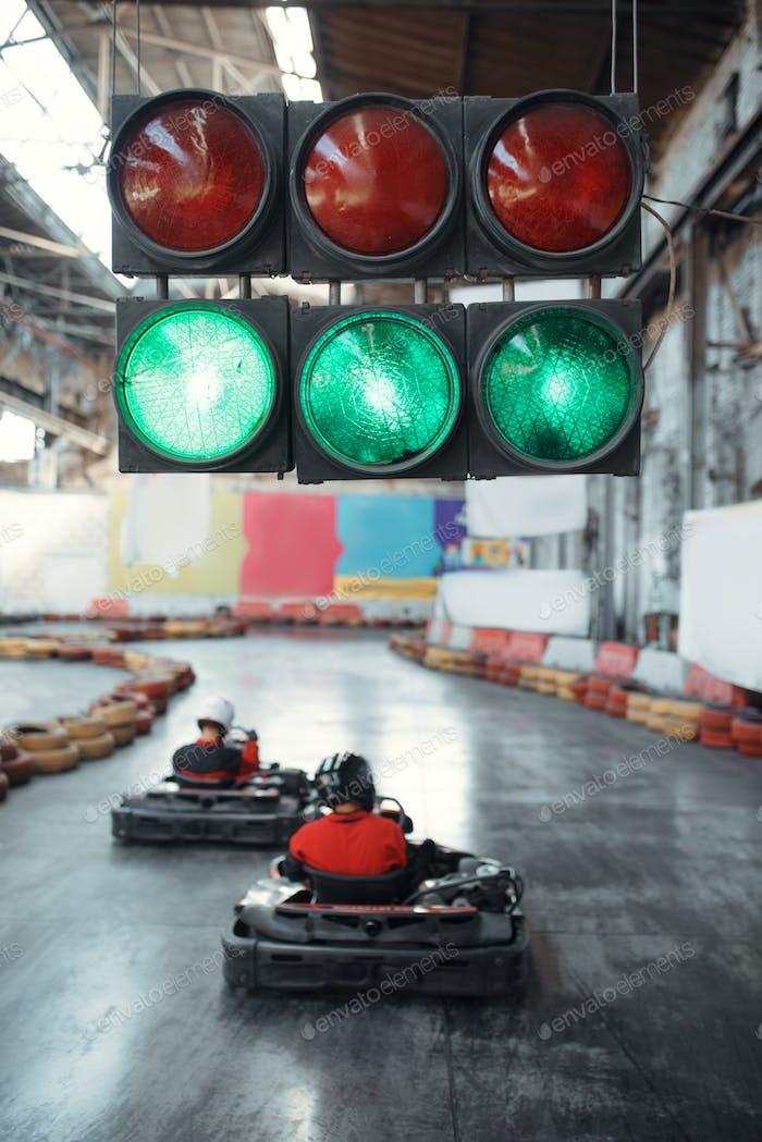 Two kart racers starts race, green traffic light