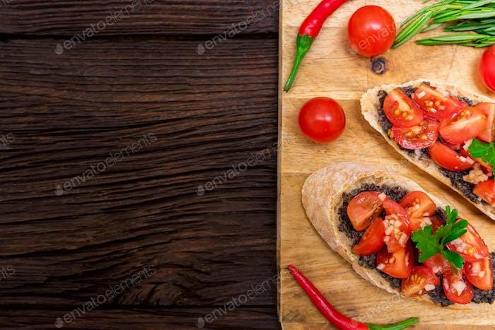 Frische leckere Bruschetta mit Trüffelsauce, Petersilie und Tomaten. Ansicht von oben