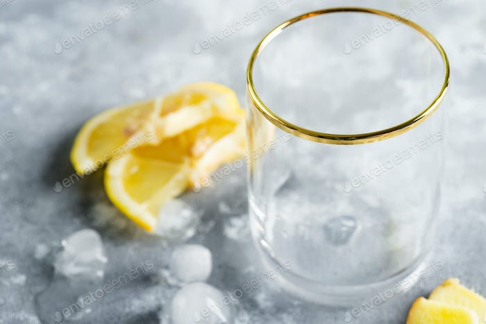 Leeres Glas für die Zubereitung von erfrischenden natürlichen kalten Cocktail oder Getränk aus Zitronenfrüchten und Eiswürfeln