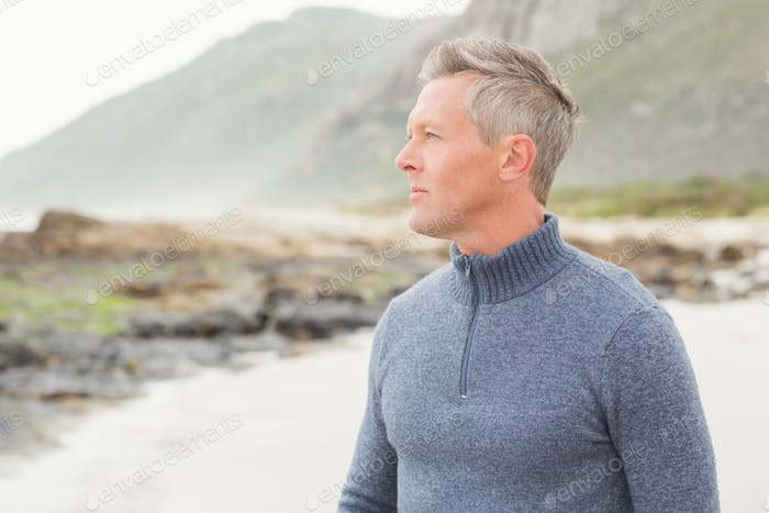 Man looking out past the shore of the beach