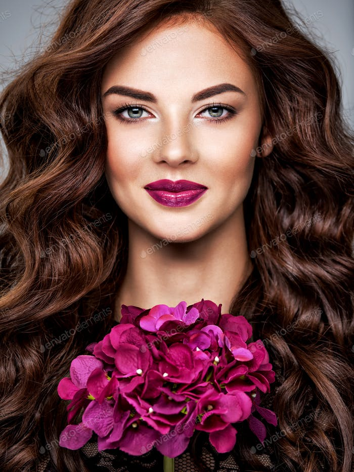 Beautiful woman with long curly hair and  purple make-up.