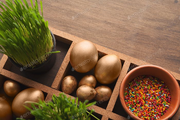 Easter composition with golden eggs, sprinkles and green grass
