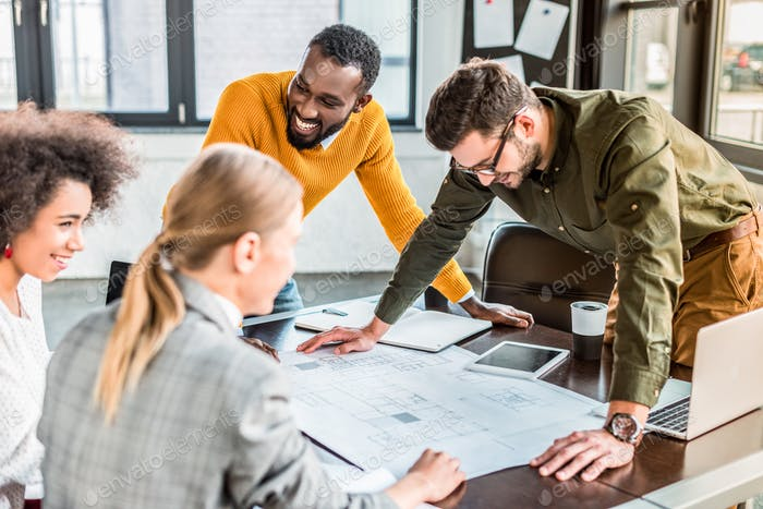 happy multicultural businesspeople with blueprint in office