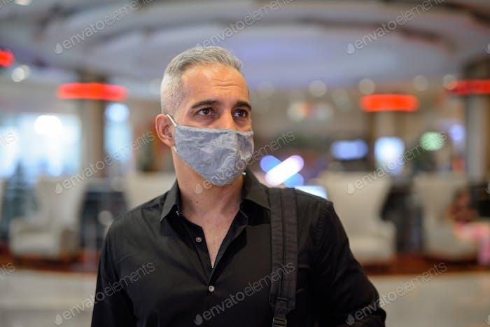 Man wearing protective facial mask to protect from covid 19 corona virus