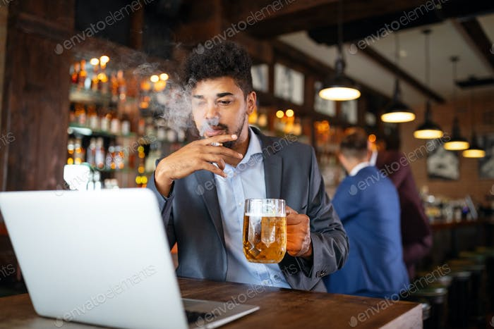 Man drinking beer and smoking cigarette while working on computer. Bad habit concept